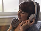 Smiling woman wearing headphones - STKF001192