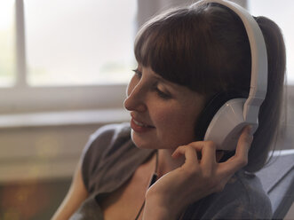 Smiling woman wearing headphones - STKF001192