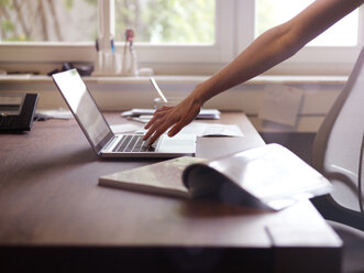 Hand at laptop and magazine on table - STKF001167