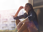 Smiling woman at open window - STKF001165