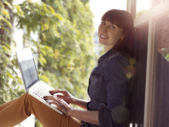 Smiling woman at open window using laptop - STKF001163