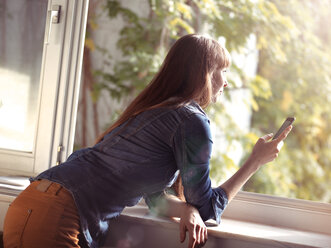Woman at open window holding cell phone - STKF001161
