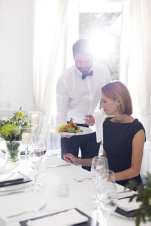 Waiter serving dinner to woman in elegant restaurant - WESTF020417
