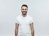 Portrait of laughing young man in front of light background - RH000457