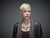 Portrait of blond young woman with tatoo in front of grey background - RH000463