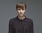 Portrait of sad young woman in front of grey background - RHF000464