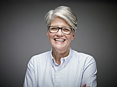 Portrait of laughing mature woman with grey hair in front of grey background - RHF000467