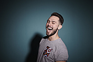 Portrait of laughing young man in front of blue background - RHF000469