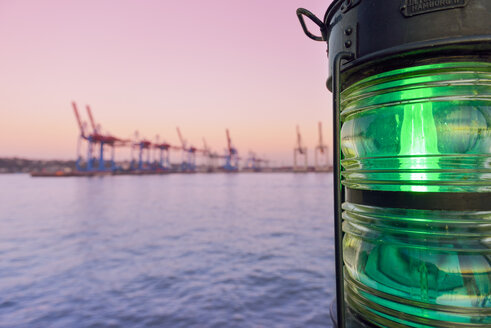 Germany, Hamburg, view to harbour at twilight with navigation light in the foreground - RJF000378
