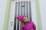 Young girl wearing pink winter jacket and cap, standing in front of entry door - MW000084