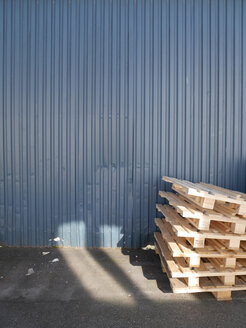 Stack of wooden pallets in front of blue steel sheet facade - JMF000304
