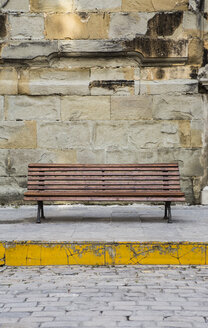 Spain, Andalusia, Tarifa, wooden bench in front of stone wall - KB000269