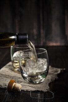Pouring whisky into a tumbler with ice - SBDF001591