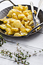 Cast iron frying pan of fried potatoes on wood - ODF000922