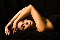 Portrait of woman lying on back in front of black background - TCF004469
