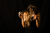 Woman disentangling her hair in front of black background - TCF004471