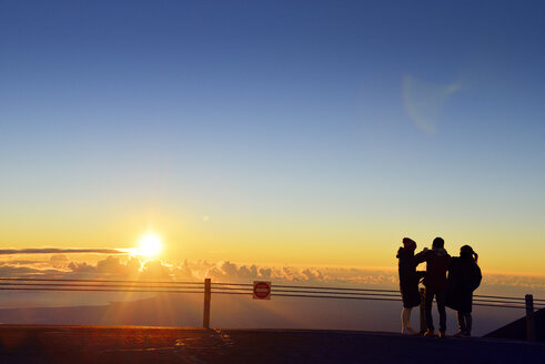 USA, Hawaii, Big Island, Mauna Kea, three tourists watching sunrise - BR000957