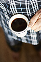 Man in pajama with cup of coffee, partial view - HAWF000548