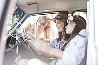 South Africa, Friends on a road trip looking at mobile phone - ZEF002773