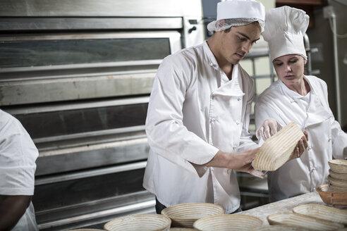 Baker preparing ceramic bowls for baking bread - ZEF003780