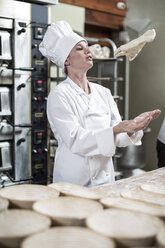 Female baker flipping dough in the air - ZEF003785