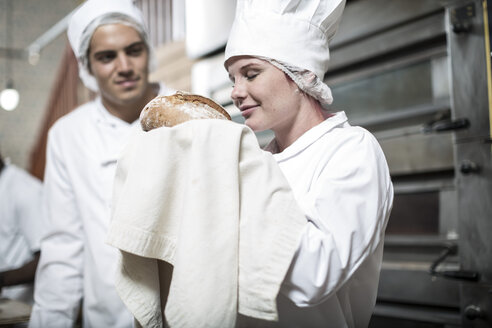 Female baker excited over baked bread fresh from the oven - ZEF003802