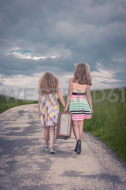 Germany, Bavaria, Two girl walking on country road carrying old suitcase, rear view - VTF000381 - Val Thoermer/Westend61