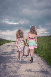 Germany, Bavaria, Two girl walking on country road carrying old suitcase, rear view - VTF000381