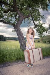 Germany, Bavaria, Girl with old suitcase waiting at roadside - VTF000384
