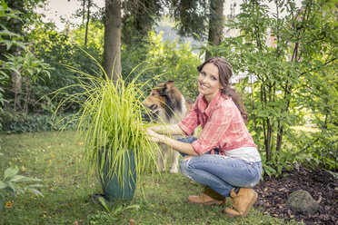 Germany, Coburg Young woman in garden with collie - VT000390