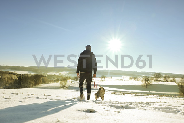 Germany, Bergisches Land, man walking dog in winter landscape - ONF000754