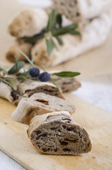 Sliced home-baked baguette with olives and dried tomatoes on wooden board - ODF000976