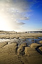 Germany, Sylt, Westerland, walkers on the beach in winter at low tide - HOHF001263