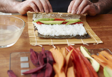 Man rolling sushi with a sweet potato, avocado and bell pepper filling - HAWF000562