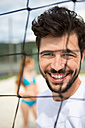 Portrait of smiling young man at net of beach volleyball field - WESTF020678