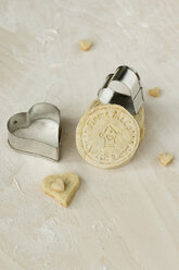Home-baked cookies and two heart shaped metal cookie cutters on light wood - MYF000804