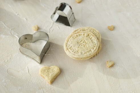 Home-baked motif cookies and two heart shaped metal cookie cutters on light wood - MYF000806