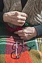 Hands of senior woman buttoning her vest while glasses lying on blanket - DEGF000110