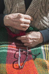 Hands of senior woman buttoning her vest while glasses lying on blanket - DEGF000110