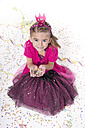 Portrait of smiling little girl masquerade as a princess holding confetti in her hands - YFF000289