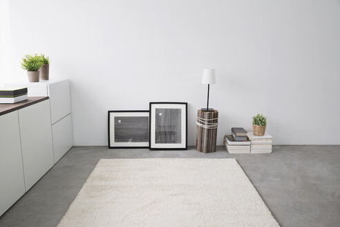 Sideboard, picture frames, stack of books, carpet and table lamp in a modern living room - PDF000673