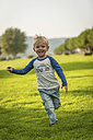 Happy boy running on meadow - PAF001199