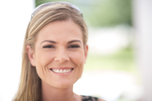 Portrait of smiling blond woman outdoors - ZEF003165