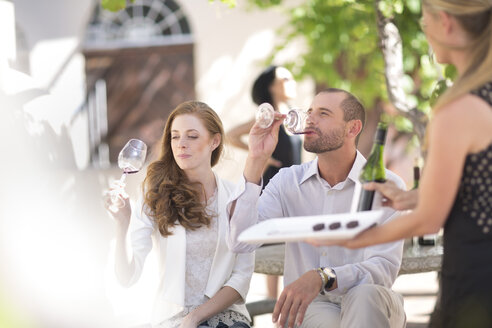 Waitress with tray and couple sitting outdoors tasting red wine - ZEF003194