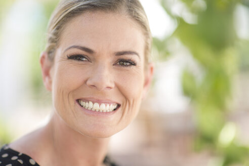 Portrait of smiling blond woman outdoors - ZEF003200