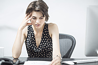 Frustrated businesswoman sitting at desk - ZEF003033