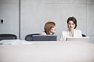 Two businesswomen using laptops in conference room - ZEF003043