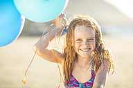 Girl on the beach smiling and holding balloons - ZEF003306