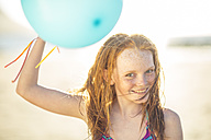 Girl on the beach smiling and holding balloon - ZEF003307