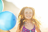 Girl on the beach smiling and holding balloons - ZEF003308